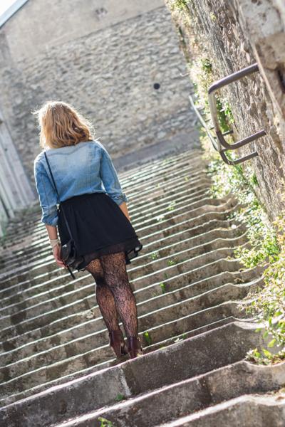 Jeune femme blonde montant un escalier en pierres